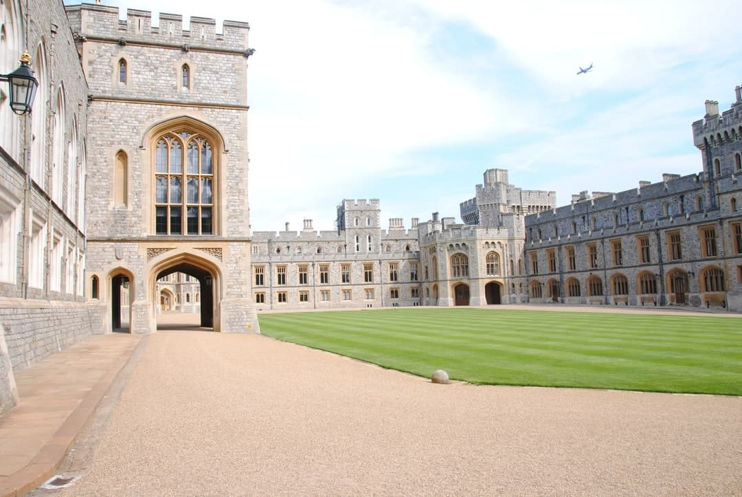 A large stone building with Windsor Castle in the background